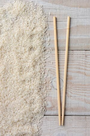 chop sticks: High angle view of chop sticks laying next to a pile of white rice on a rustic wood table. Stock Photo
