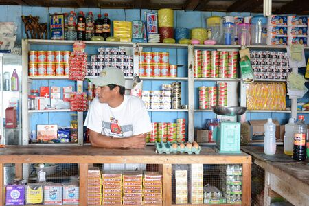 general store: SANTA ANA VILLAGE, PERU - OCTOBER 16, 2015: Shopkeeper in his bodega. The small general store is a common sight in small villages in the Peruvian Amazon.
