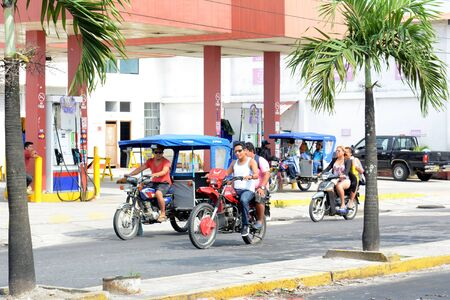autorick: IQUITOS, PERU - OCTOBER 17, 2015: MotoKars and motorcycles on Iquitos street. Motorcycles and MotoKars are the common form of transportation in the Amazon. Editorial