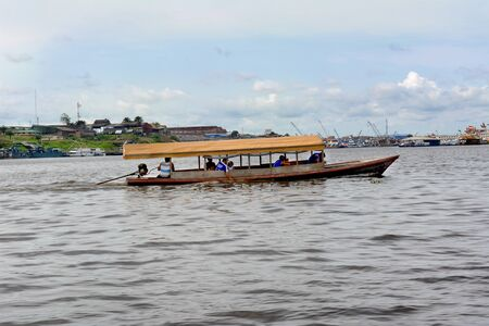 water transportation: IQUITOS, PERU - OCTOBER 11, 2015: Water Taxi on the Itaya River. The water taxi is an important and vital means of transportation in the Peruvian Amazon.