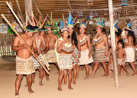 IQUITOS, 페루 -2010 년 10 월 18 일 : 전통적인 춤을 수행하는 페루의 보라 공동체. 부족은 전통적인 공동체 오두막에서 에콰도르 무용으로 옮겼습니다.