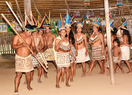 RELOCATED: IQUITOS, PERU - OCTOBER 18, 2015: Bora community of Peru performing traditional dance. The tribe relocated from Ecuador dance in a traditional community hut.