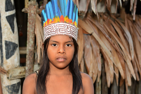 RELOCATED: IQUITOS, PERU - OCTOBER 18, 2015: A young girl of the Bora Tribe in Peru. Portrait of a native girl in traditional costume standing in front of a typical hut.