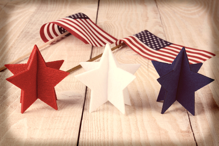 Closeup of red, white and blue stars on a wood table with two American flags in the background. Vignette