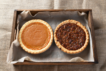 pumpkin pie: High angle view of a fresh baked pumpkin pie and a pecan pie in a wood box on burlap covered table, for Thanksgiving feast. Stock Photo