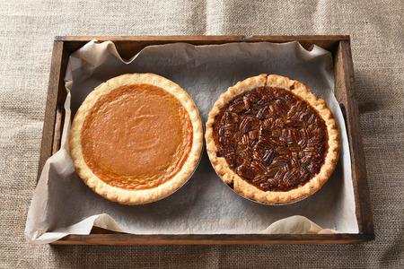 pecan pie: Vista de ángulo alto de un pastel de calabaza al horno fresco y un pastel de nuez en una caja de madera en la mesa de arpillera cubierto, durante la fiesta de Acción de Gracias.