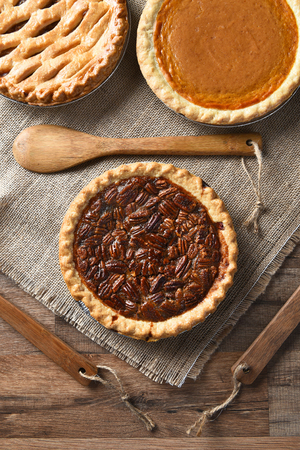 sweet and savoury: High angle vertical view of three pies for A thanksgiving feast. Pecan in the front with Apple and Pumpkin pies in the background. On burlap with wood utensils.