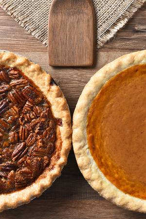 utensils: High angle vertical of half of a Pecan Pie and a Pumpkin Pie. The fresh baked pies are on a wood table with burlap table cloth and wood utensil.