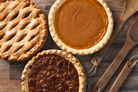 感謝祭の休日の饗宴のための 3 つのパイの俯瞰。ピーカン ナッツ、リンゴ、カボチャの木のテーブルの水平方向の形式
