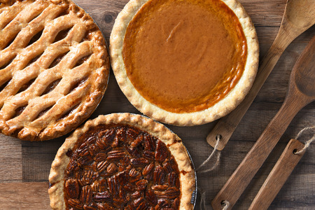 pumpkin pie: Overhead view of three pies for a Thanksgiving Holiday feast. Pecan, Apple and Pumpkin in horizontal format on wood table