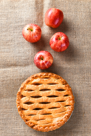pastry crust: High angle view of a fresh baked apple pie for the Thanksgiving holiday, Vertical format on a burlap surface.