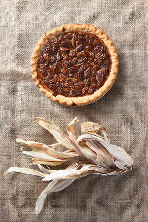 high angle view: Vertical high angle view of a pecan pie on burlap with corn husks.