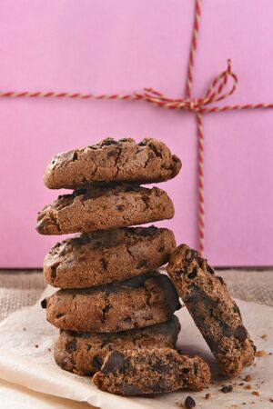 chocolate treats: Closeup of a stack of chocolate chocolate chip cookies in front of a pink bakery box.