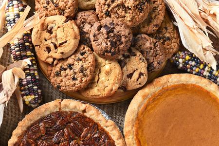 Primer plano de pasteles y galletas para un día de Acción de Gracias postres de fiesta. Pecan Pie, pastel de calabaza, chispas de chocolate, pasas avena y maíz indio adornan la mesa.