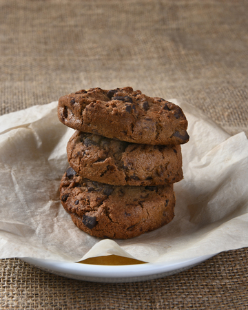 chocolate treats: Closeup of three chocolate chocolate chip cookies on a plate. The delicious fresh baked treats and plate are on a burlap table cloth.