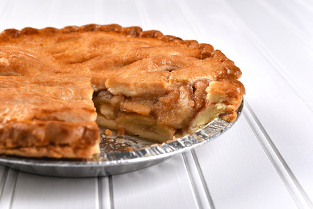 apple pie: Closeup of a fresh baked apple pie with a slice missing. Shallow depth of field on a white bead board background.