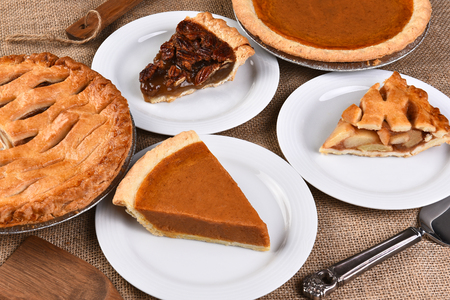 High angle view of whole pies and plates with slices. Traditional Thanksgiving desserts include, Pecan Pie, Apple Pie and Pumpkin Pie.