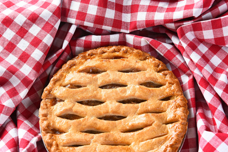 red cloth: Closeup of a fresh baked Apple Pie surrounded by a red and white checked table cloth. Stock Photo