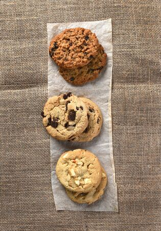 high angle view: High angle view of three small stacks of fresh baked holiday cookies on a strip of parchment paper on burlap covered table. High angle view in vertical format. Stock Photo