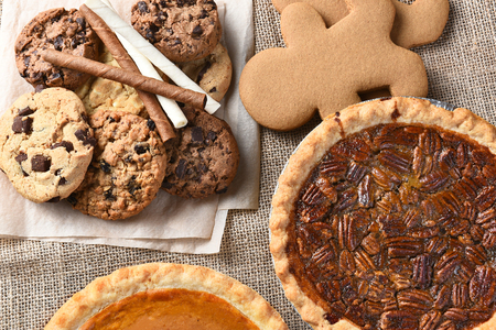 american dessert: Assorted holiday desserts including:  gingerbread, pumpkin pie, pecan pie, chocolate chip and oatmeal raisin cookies, Stock Photo