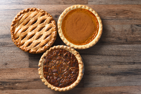 dessert table: Three pies for Thanksgiving on a wood surface. The desserts include apple, pumpkin and pecan pies - all traditional treats for the American Holiday. Stock Photo