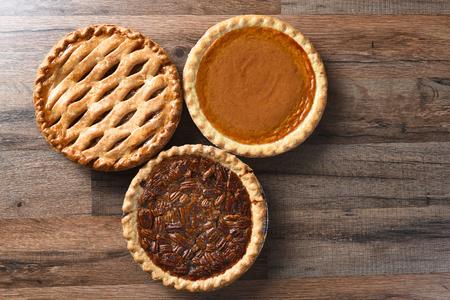 Tres empanadas de acción de gracias en una superficie de madera. Los postres incluyen manzana, calabaza y tartas de nuez - todos los dulces tradicionales de la Casa de América. Foto de archivo