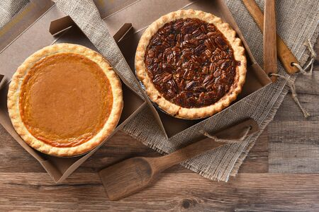 sweet and savoury: A pumpkin Pie and Pecan Pie in open bakery boxes on burlap and wood surface with wood utensils.