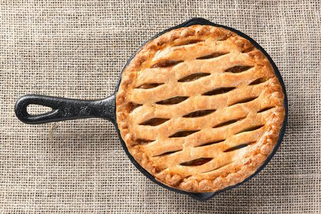 high angle view: High angle view of a skillet baked apple pie n a burlap table cloth. Stock Photo