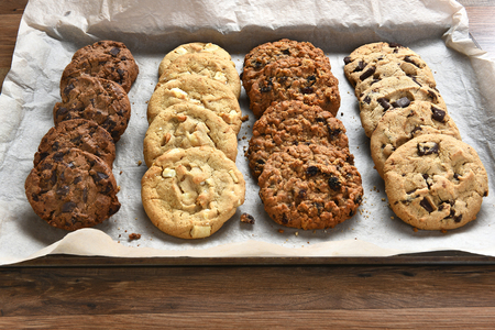 cookie sheet: Closeup of a tray of fresh baked cookies, Chocolate Chip, oatmeal raisin Chocolate and white chocolate chip cookies on baking sheet and parchment paper.