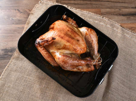 entree: High angle view of a cooked turkey in a roasting pan. The golden brown Thanksgiving entree is in a black pan on a burlap table cloth.