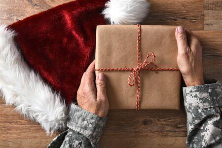 soldado: Primer plano de un soldado que sostiene un regalo de Navidad en una mesa de madera con un sombrero de Santa. Foto de archivo