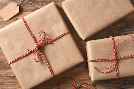 three presents: High angle view of three plain brown paper wrapped Christmas Presents on a rustic wood table. Stock Photo