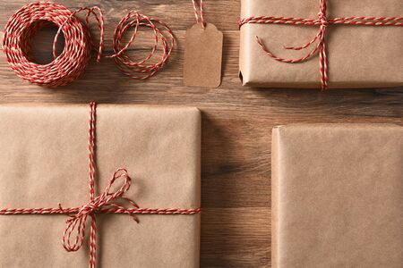 friendly: Christmas presents wrapped with eco friendly and recyclable paper and cord. High angle closeup in horizontal format.