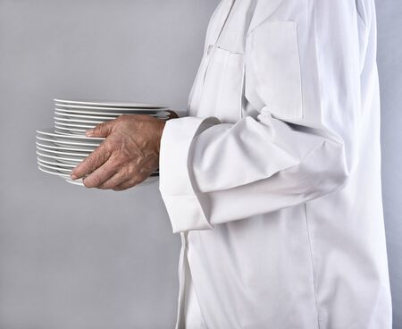 carrying: Closeup side view of chef carrying a stack of plates. The unrecognizable man is wearing a white coat holding, white plates against a light gray background. Stock Photo