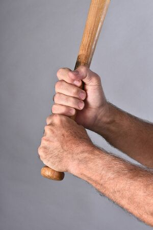 batters: Closeup of a baseball batters hands holding a wood bat. Vertical format against a gray background.