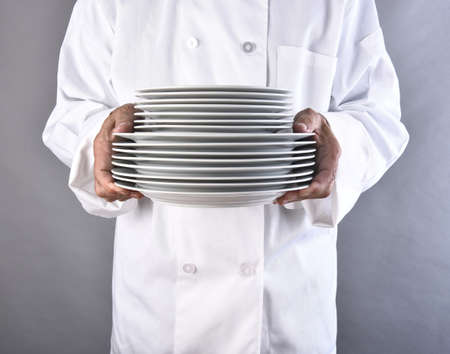 Closeup of a chef holding a stack of white plates. The man is unrecognizable. Square format against a gray background. Stock fotó