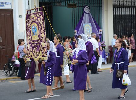 IQUITOS, PERU - OCTOBER 17, 2015: El Senor de los Milagros Procession. To celebrate a miracle purple-robed devotees follow the image through the streets.