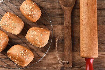 sesame seed: Overhead view of a rack of Sesame seed dinner rolls next to a wooden spatula and rolling pin.