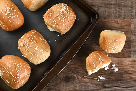 sesame seed bun: High angle view of fresh baked sesame seed dinner rolls on a baking sheet. A bun broken in half is on the table.