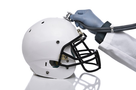 A football helmet and doctors hand holding a stethoscope on the crown of the helmet. Sports Concussion Concept, and related conditions, CTE, Alzheimers, Parkinsons.