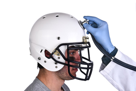 A football player wearing a helmet with doctors hand holding a stethoscope on the crown of the helmet. Sports Concussion Concept, and related conditions, CTE, Alzheimer's, Parkinson's. Standard-Bild