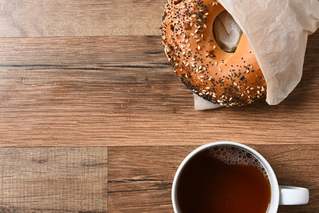 Fresh bagel and hot cup of coffee on a rustic wood table with copy space. Stock Photo