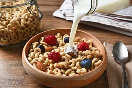 Vista de ángulo alto de un tazón de cereal de desayuno con arándanos, frambuesas y frutos secos. Una botella de leche se vierte en el recipiente
