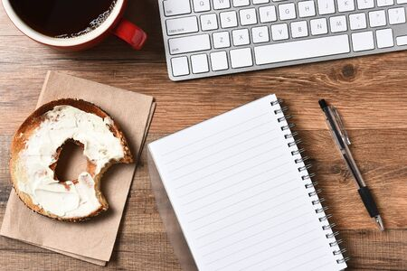 telecommute: A bagel with cream cheese and a bite taken out next to a computer keyboard and a pad and pen. A cup of coffee in the upper corner, Horizontal for a high angle. Stock Photo