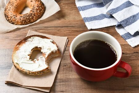 telecommute: A fresh cup of coffee and a bagel with cream cheese on a wood table.