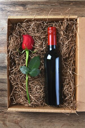 packing material: A single red rose and a bottle of wine in a cardboard box filled with packing material. High angle shot. Valentines  Love  Romance Concept. Stock Photo