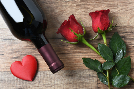 love rose: A wine bottle and two red roses and heart on a rustic wood table. Overhead view in horizontal format. Valentines Day Concept.