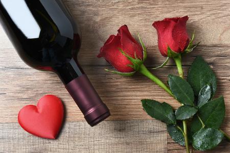 rosas rojas: Una botella de vino y dos rosas rojas y el coraz�n en una mesa de madera r�stica. Vista de arriba en formato horizontal. Concepto del d�a de San Valent�n.