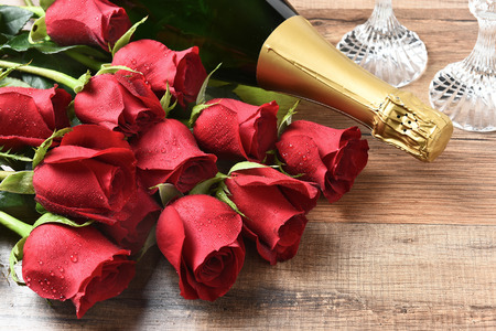 long stem roses: Closeup of a bottle of champagne and red roses on a wood table. Valentines Day  Love concept. Stock Photo
