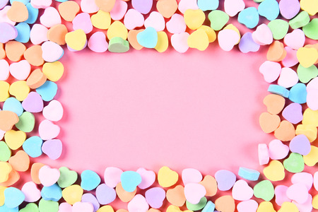 high angle shot: High angle shot of Valentines Day candy hearts on a pink background with copy space. The hearts form a frame around the pink background.